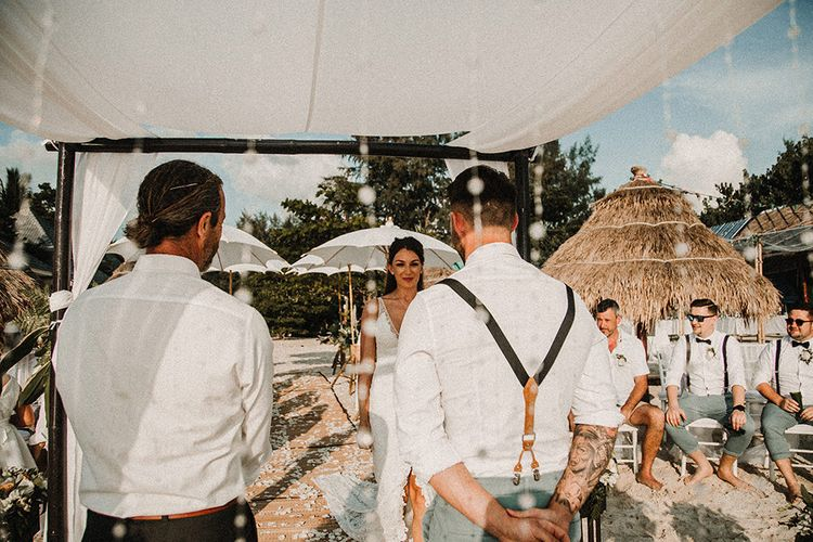 Wedding Ceremony | Bridal Entrance in Grace Loves Lace Gia Gown | Groom in Turned Up Trousers, Bow Tie & Braces from Topman | Tropical Destination on the Beach at Nice Sea Resort, Koh Phangan Thailand Planned by Phangan Weddings | Carla Blain Photography