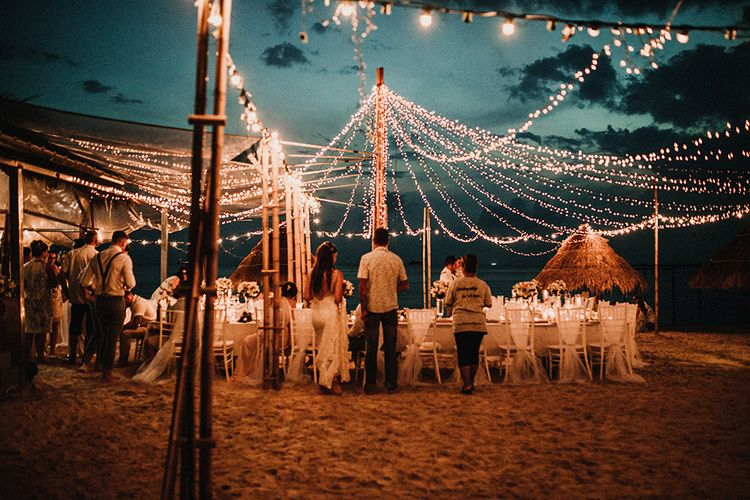 Outdoor Reception | Fairy Light Canopy | Bride in Grace Loves Lace Gia Wedding Dress | Groomsmen in Turned Up Trousers, Bow Ties & Braces from Topman | Tropical Destination on the Beach at Nice Sea Resort, Koh Phangan Thailand Planned by Phangan Weddings | Carla Blain Photography