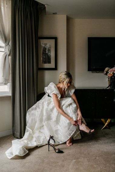Bride Putting on Black Ankle Strap Sandals in Jesus Peiro Wedding Dress