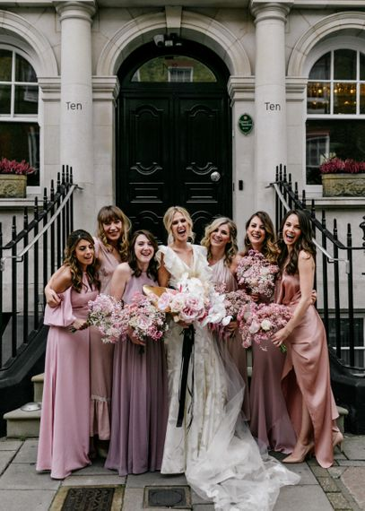 Stylish Bridal Party Portrait in Pink Bridesmaid Dresses and Ruffle Wedding Dress