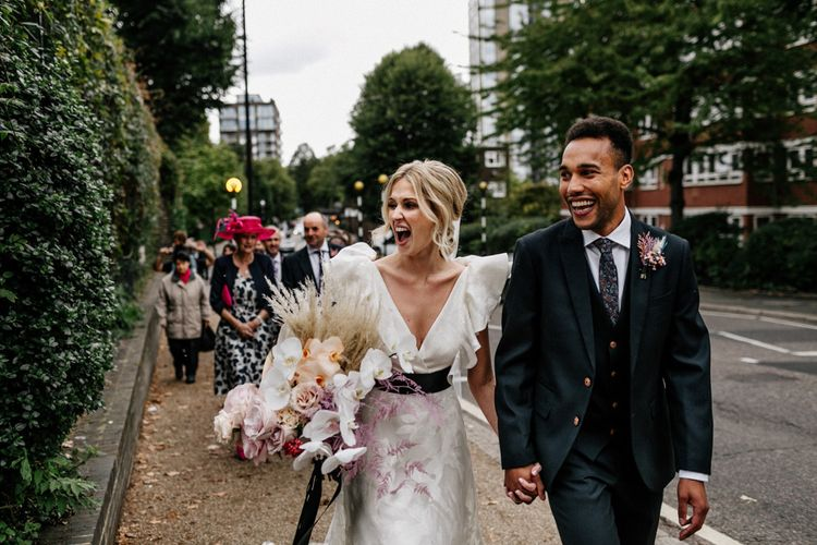 Stylish Bride and Groom Walking From Their Ceremony to Their Reception in Ruffle Wedding Dress and Navy Suit