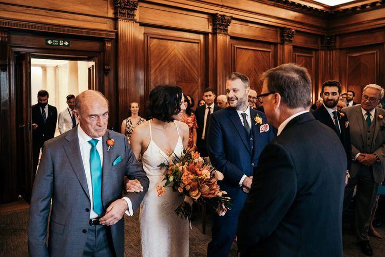 Bride Greets Groom At London Ceremony Venue Holding Orange Wedding Flowers