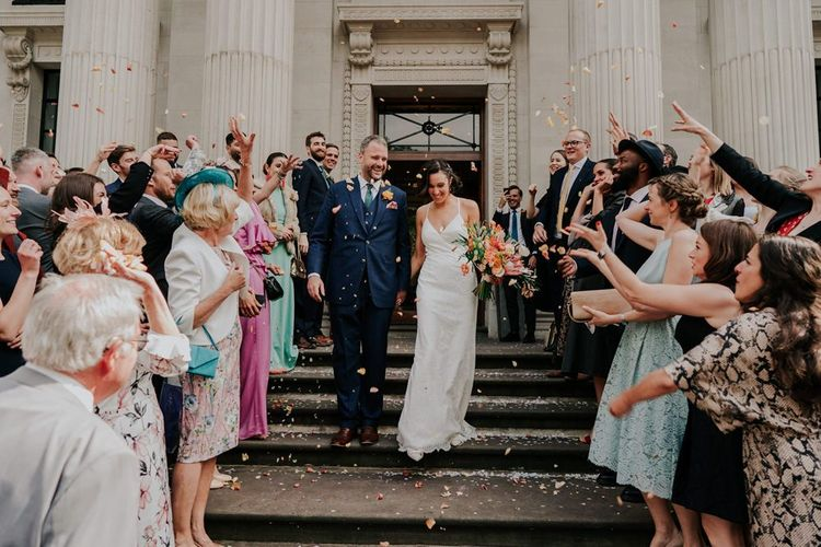 Bride and Groom Confetti Exit With Bride Carrying Orange Wedding Flowers