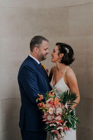 Bride Holds Orange Wedding Flowers With Embellished Hair Accessory