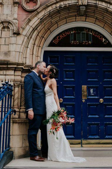 Bride Kisses Groom Holding Orange Wedding Flowers