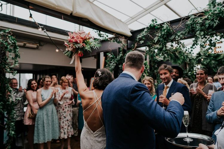 Bride Celebrates Lifting Orange Wedding Flowers
