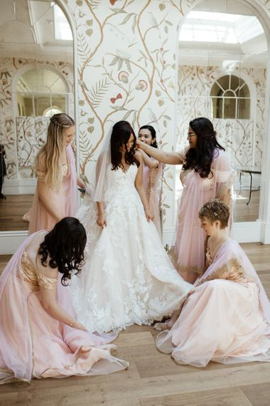 Bride in strapless wedding dress with bridal party in pink saris