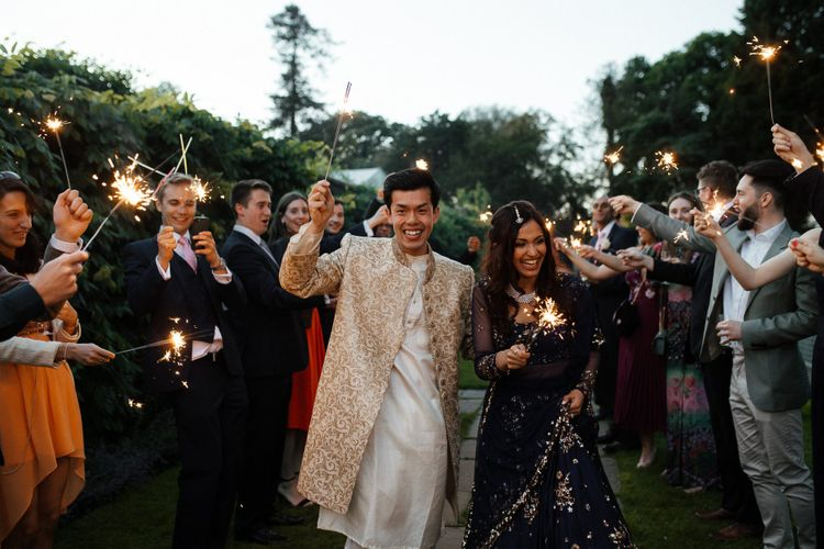Sparkler exit for groom and bride in traditional Indian wedding dress