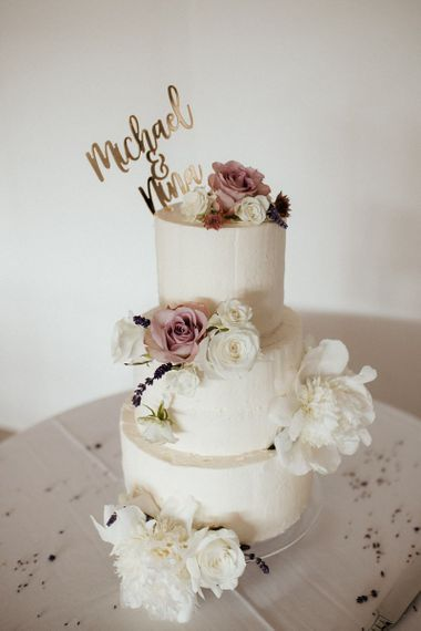 White wedding cake with pink flower decor