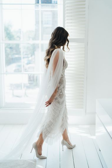 Bride wearing a custom made embellished Emma Beaumont dress with watteau train