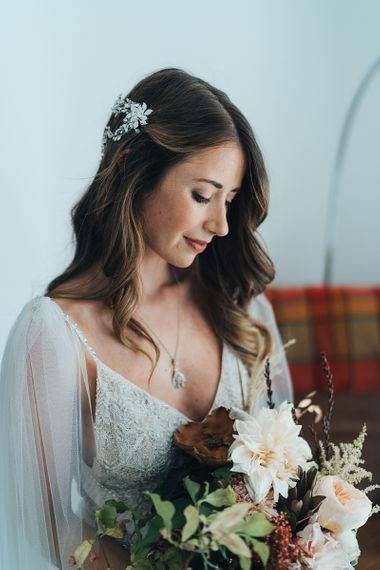 Bride wearing an embellished hair accessory with a peach bouquet using fresh and dried flowers