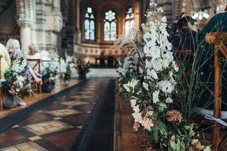Church ceremony with balloon installation and fresh aisle decor of seasonal foliage and cafe au lait dahlias
