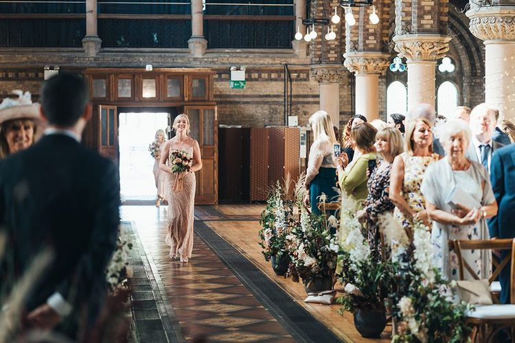 Bridesmaids wearing peach embellished dresses walking down the aisle at church ceremony with fresh foliage decor