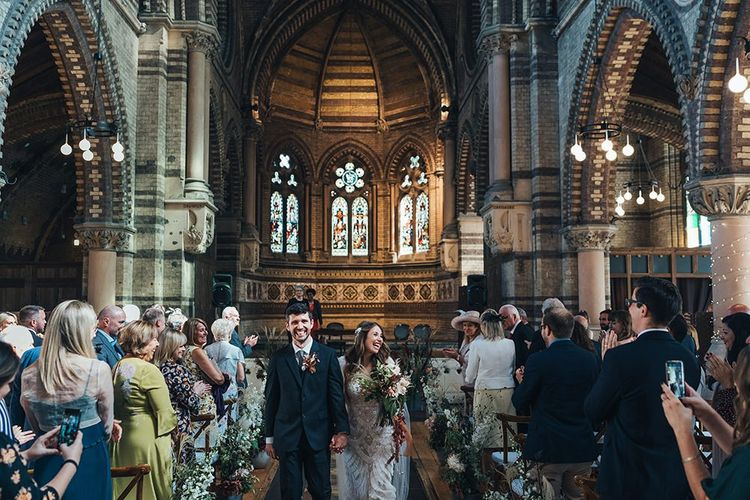 Bride and groom tie the knot at church ceremony wearing custom made embellished dress and peach wedding flowers mixed with dried foliage