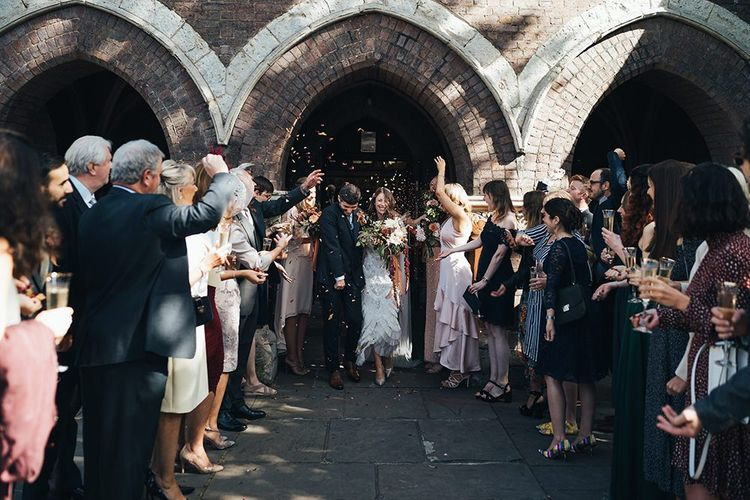 Church confetti moment with bride wearing embellished dress and peach wedding flowers tied with vintage trim