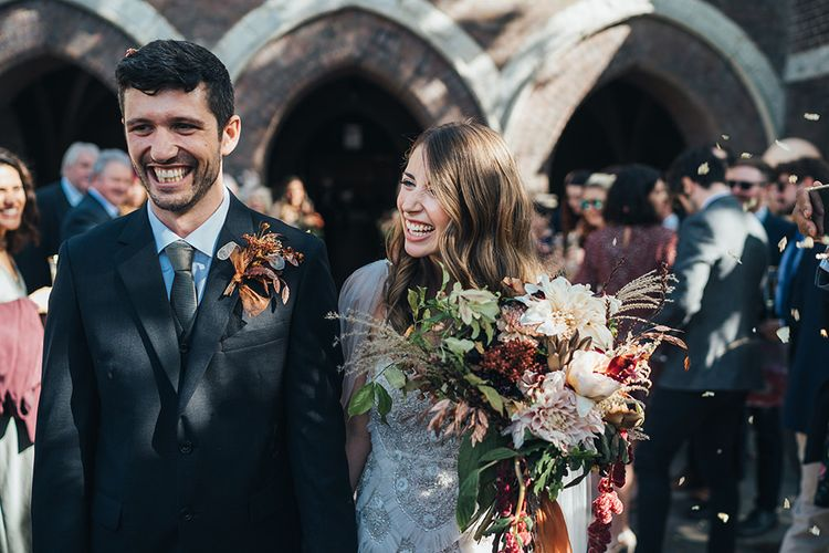 Groom wearing dried floral buttonhole arrangement and bride holding peach wedding flowers tied with vintage trim