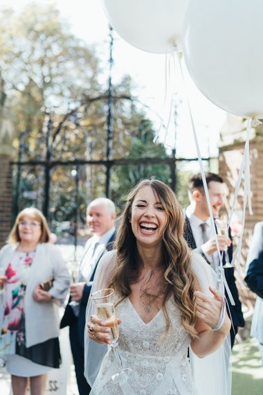 Bride wearing embellished custom made dress with watteau train and balloon installation