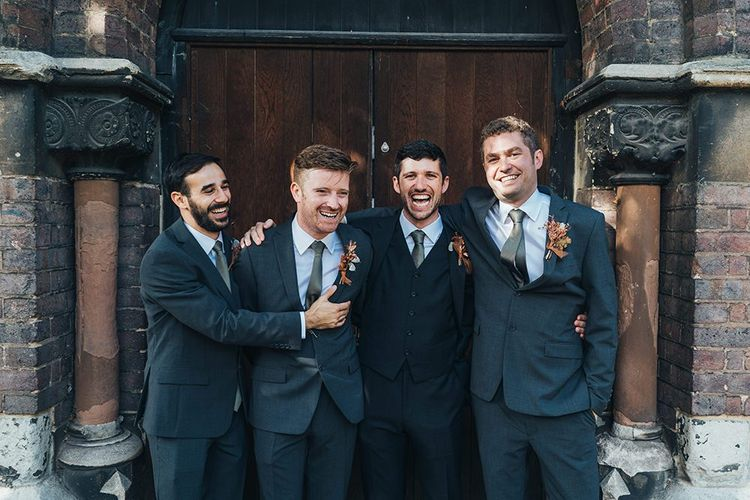 Groom and his groomsmen at church ceremony wearing dried floral button hole arrangements