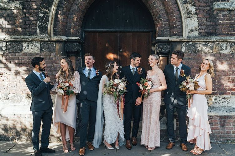 Bride and groom with their guests at church ceremony with balloon installation and peach wedding theme