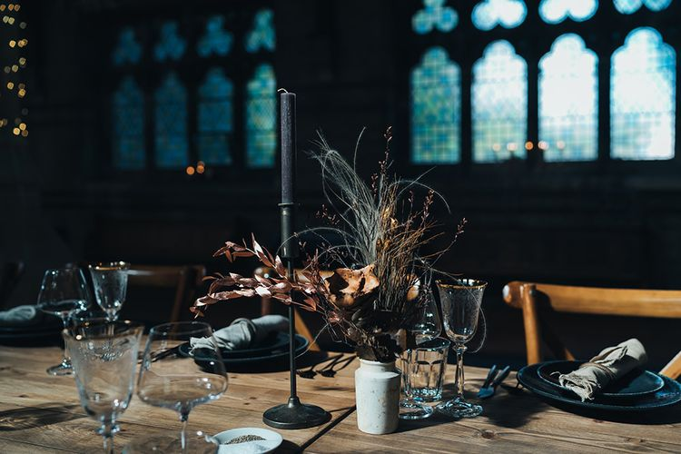 Long tables styled with dark and earthy tones mixed with metallic touches at St Stephens Trust wedding reception with balloon installation