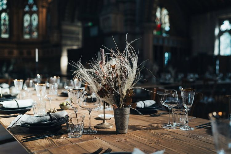 Long tables styled with dark and earthy tones mixed with metallic touches at St Stephens Trust wedding reception with dried flower arrangements