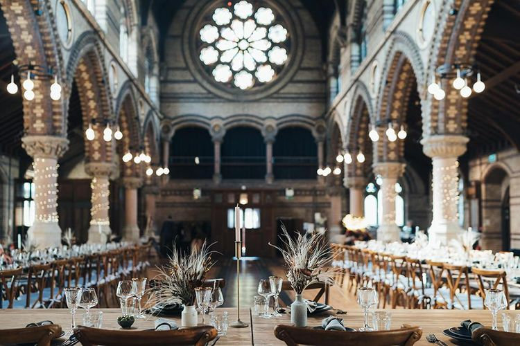 Long tables styled with dark and earthy tones mixed with metallic touches at St Stephens Trust wedding reception with balloon installation  and dried foliage decor