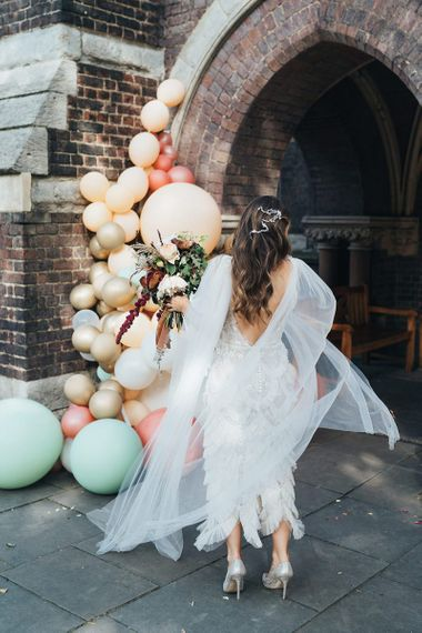 Back of brides beautifully embellished Emma Beaumont dress with beaded hair accessory and balloon installation