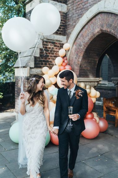 Bride and groom tie the knot at relaxed autumn wedding with dried floral decor and balloon installation