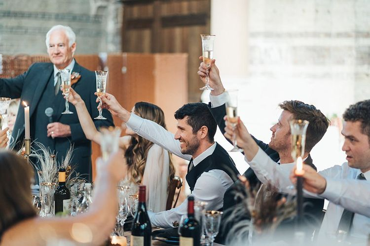 Bride and groom raise a glass at their St Stephens Trust reception with relaxed styling and dried floral decor