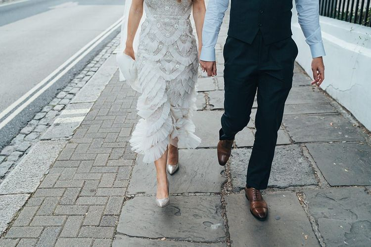 Bride wearing glitter stiletto shoes and embellished dress with the groom stealing a moment