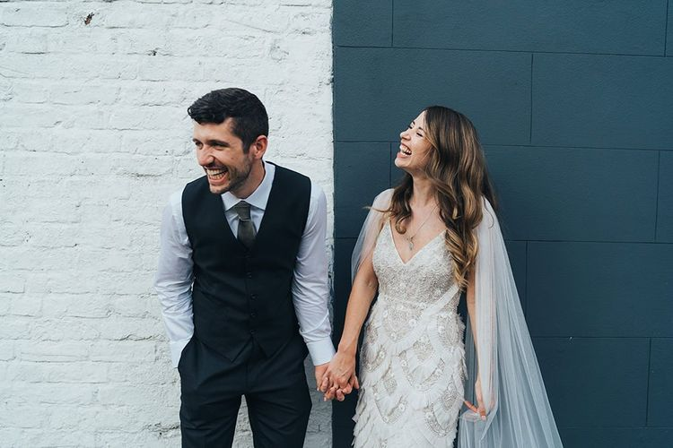 Groom in waistcoat and bride wearing custom made Emma Beaumont dress with detachable train