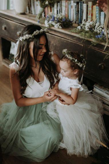 Bridesmaid in blue tulle skirt holding the flower girl