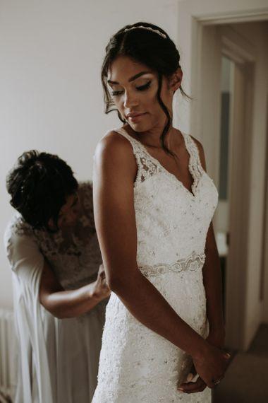 Bride putting on her dress on wedding morning