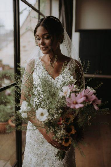 Bride holding her wildflower bouquet on wedding morning