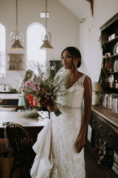 Stunning bride standing in the kitchen on the wedding morning of home garden wedding