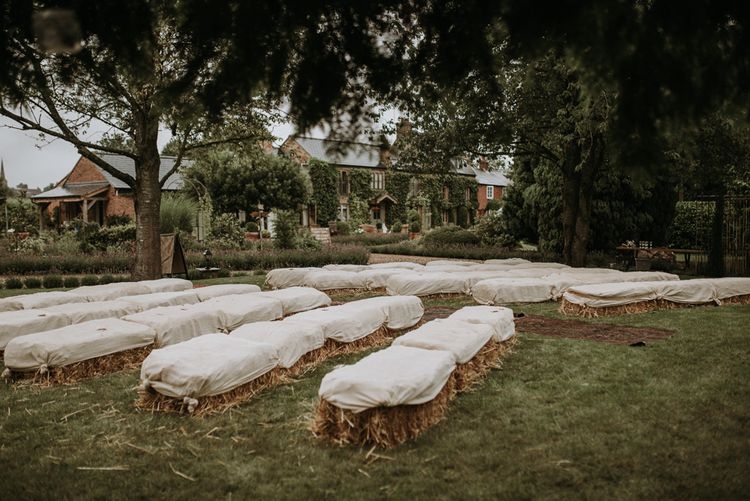 Hay bale seating at home using garden for wedding ceremony
