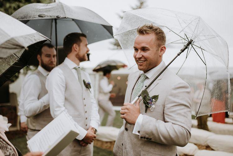 Groom in beige suit under clear umbrella