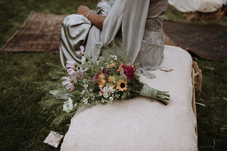 Wildflower wedding bouquet resting on a hay bale