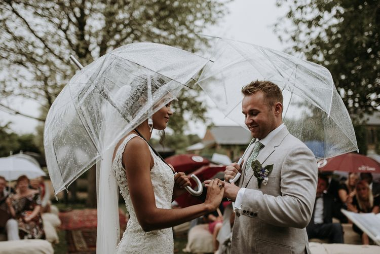 Bride and groom exchanging rings at home garden wedding