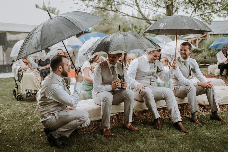 Groomsmen sitting under umbrellas at rainy outdoor garden wedding ceremony