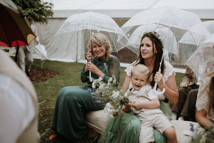 Bridal party sitting under umbrellas at rainy outdoor wedding ceremony