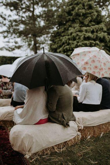 Wedding guests huddled under umbrellas at rainy outdoor wedding