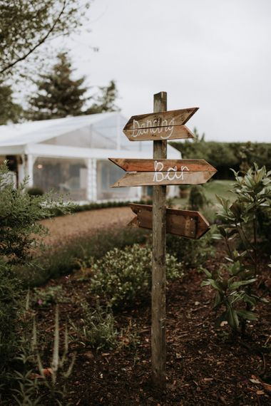wooden sign post in home garden for wedding celebration