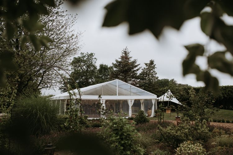 Clear span marquee reception in home garden for wedding celebration