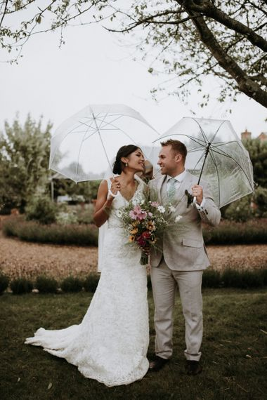 Bride and groom standing under umbrellas after home garden wedding ceremony