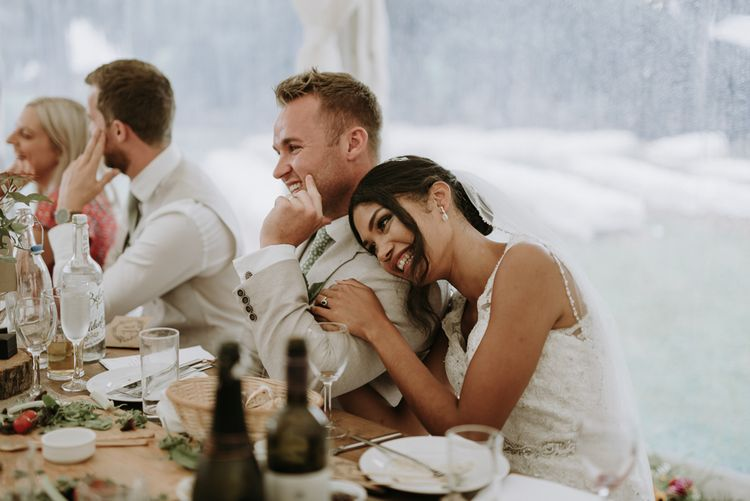 Bride and groom embracing during wedding reception speeches
