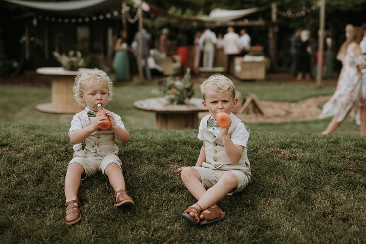 page boys drinking juice in the garden