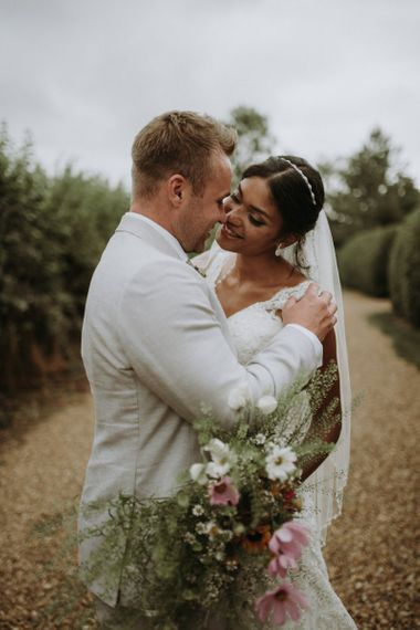 Intimate bride and groom portrait with wildflower bouquet