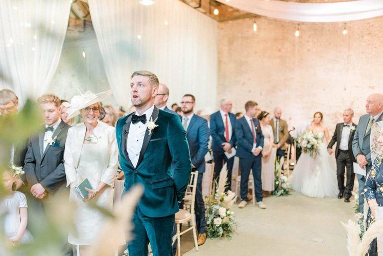 Groom in blue velvet jacket waits for bride in detachable skirt wedding dress