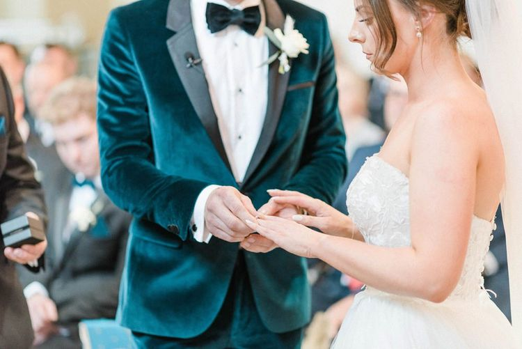 Bride in detachable skirt wedding dress exchanging rings with groom